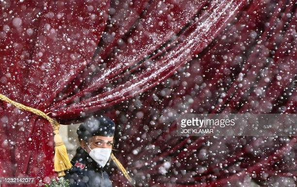 Snow falls as a police officer stands guard near the entrance of the Grand Hotel in Vienna on April 6 where diplomats of the EU, China, Russia and...