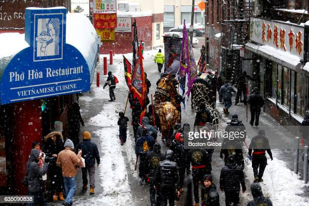 Snow falls as lion dancers make their way through Boston's Chinatown neighborhood during Chinese New Year celebrations on Feb 12 2017