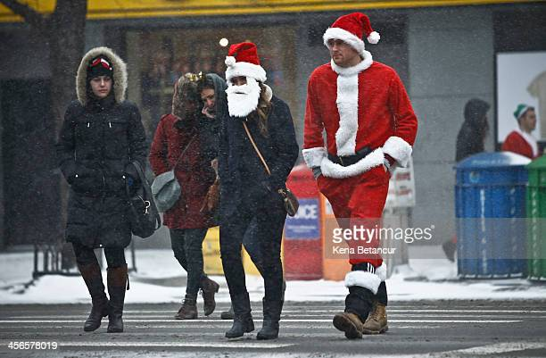 Snow falls as revelers dressed as Santa Claus walk in Manhattan during the annual SantaCon bar crawl event on December 14 2013 in New York City The...
