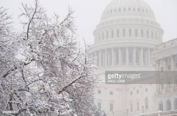 Snow falls at the US Capitol during a snow storm in Washington DC March 21 2018 The fourth Noreaster in less than three weeks Winter Storm Toby is...