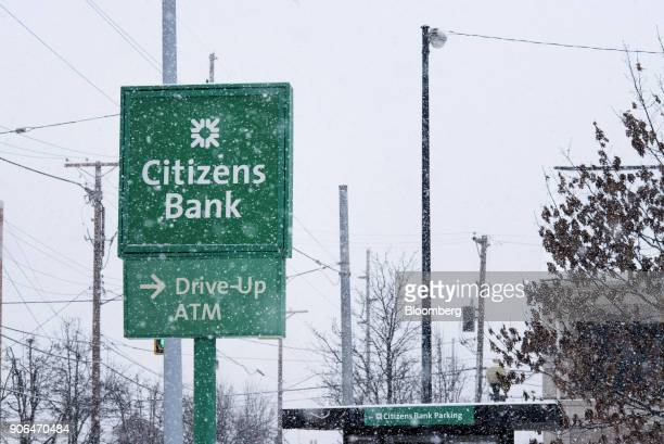 Snow falls in front of signage outside a Citizens Financial Group Inc bank branch in downtown Portsmouth Ohio US on Tuesday Jan 18 2018 Citizens...