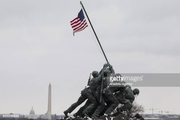 Snow falls on the Iwo Jima Memorial and the National Mall behind it during an abnormally late snow fall in Washington United States on March 14 2017...