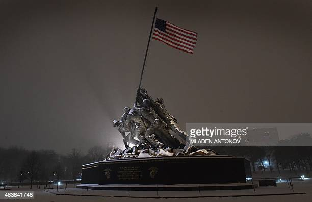 Snow falls on the Iwo Jima memorial in Washington DC on February 16 2015 The eastern United States braced for an arctic onslaught as forecasters...