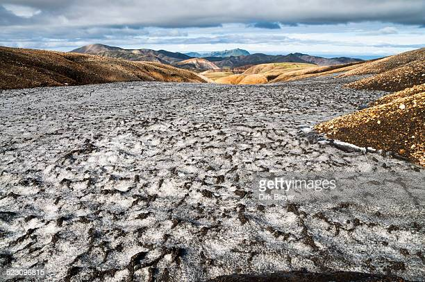 Snow field colored black from ashes, rhyolite mountains, Landmannalaugar, Fjallabak Nature Reserve, Highlands of Iceland, Iceland, Europe