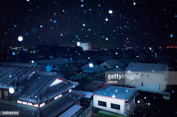 Snow flakes falling down on the town