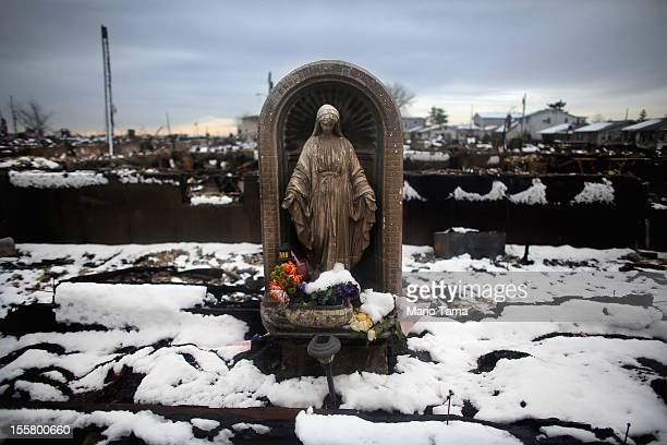 Snow from a Nor'Easter storm coats homes burned in the aftermath of Superstorm Sandy amid a statue of the Virgin Mary on November 8, 2012 in the...