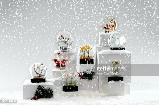 snow globes in snow against white background - fake snow stock pictures, royalty-free photos & images