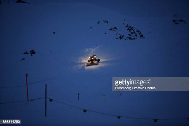 A snow groomer illuminates the piste as it flattens the snow on a ski run in Davos