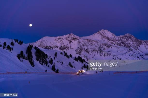 schneefräser am abend auf skipiste - schneefahrzeug stock-fotos und bilder