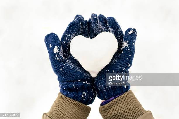 Snow heart on hands with gloves
