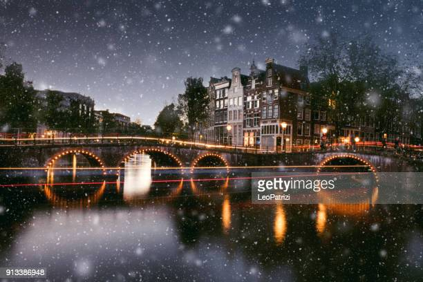 snow in amsterdam canals at night in winter - amsterdam stock pictures, royalty-free photos & images