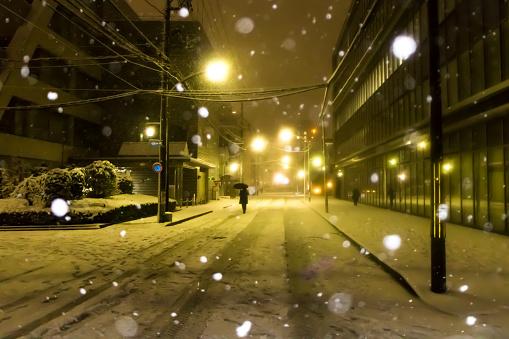 Snow is falling in Tokyo downtown street at night in 2018 winter, Japan. - gettyimageskorea