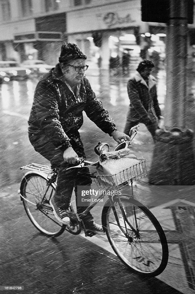 "APR 1 1977, APR 2 1977; Snow Is No Joke; This bicyclist finds himself ""out in the cold"" Friday evening as he pedals his cycle near 15th and California Sts. in Downtown Denver. He was caught in the snow when an April Fool's Day storm arrived in the Denver  : News Photo"