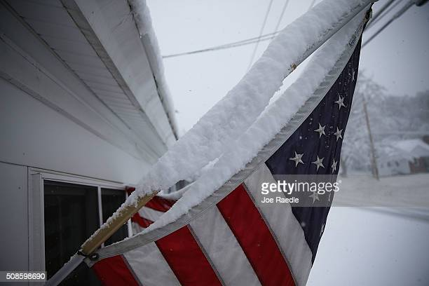 Snow is seen gathered on an American flag during a snow storm as primary voters make up their minds on a Presidential candidate on February 5 2016 in...