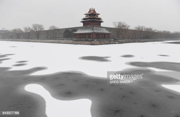 TOPSHOT Snow is seen in the moat surrounding the Forbidden City during a snowfall in Beijing on February 21 2017 / AFP PHOTO / GREG BAKER