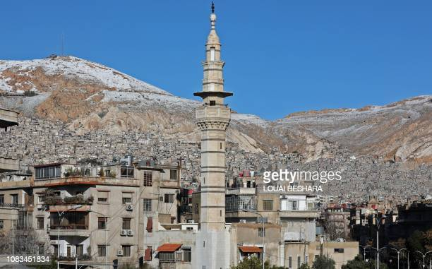 Snow is seen on Mount Qasion in the Syrian capital Damascus on January 17, 2019. - Freezing temperatures and the lack of medical care have killed at...
