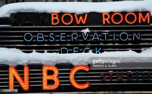 Snow is seen on the neon sign for NBC studios and the Rainbow Room in New York on February 2, 2021. - A huge snowstorm has brought chaos to the...