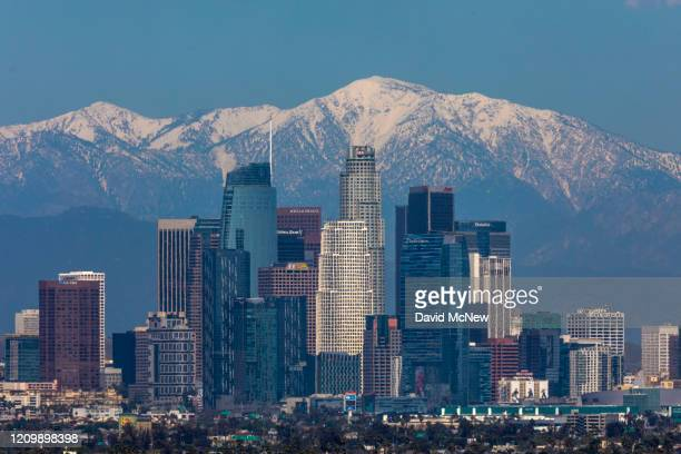 Snow is seen on the San Gabriel Mountains beyond downtown Los Angeles under a clear sky after weeks of storms and reduced traffic as coronavirus...