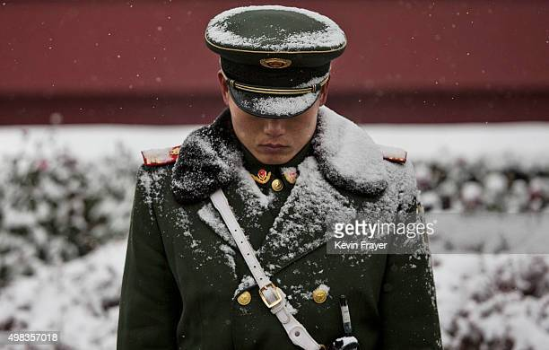 Snow is seen on the uniform of a Chinese paramilitary police officer as he stands guard outside Tiananmen Gate during a snowfall on November 22 2014...