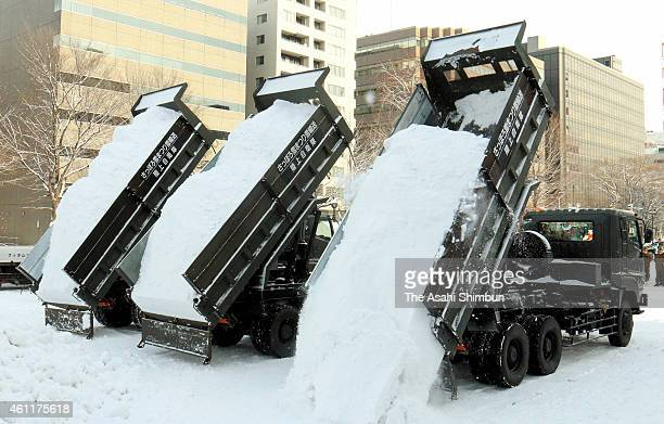 Snow is unloaded from the Japan Ground SelfDefense Force trucks in preparation for the Sapporo Snow Festival on January 7 2014 in Sapporo Hokkaido...
