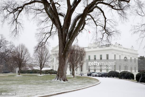 Snow just begins to cover the ground on the North Lawn of the White House in Washington DC January 7 2017 / AFP PHOTO / Tasos KATOPODIS