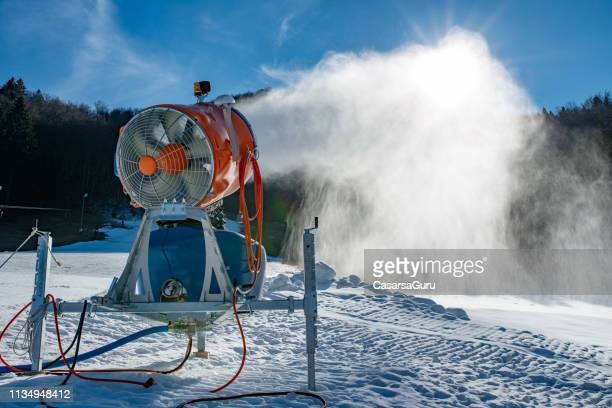 snow machine blowing artificial snow over a ski slope on a sunny day - fake snow stock pictures, royalty-free photos & images