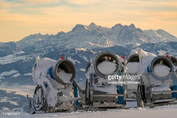 snow machine, snow gun, snow cannon in the sun with view into the valley - ski resort stock pictures, royalty-free photos & images