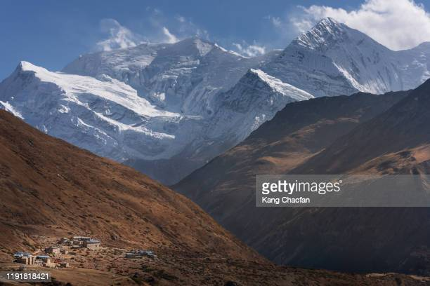 snow mountain and village view along annapurna circuit trek, nepal - annapurna south stock pictures, royalty-free photos & images