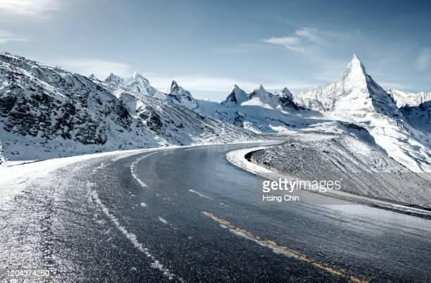 snow mountain road - straßenverkehr stock-fotos und bilder
