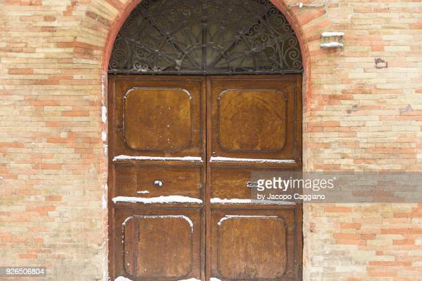 snow on a closed wooden door - jacopo caggiano stock pictures, royalty-free photos & images