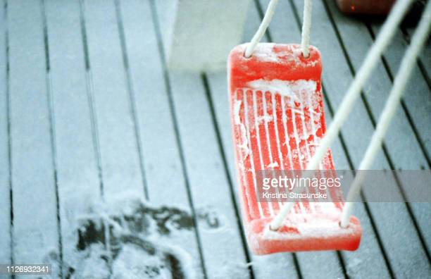 snow on a plastic swing - kristina strasunske stock photos and pictures