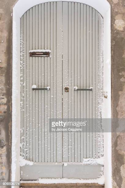 Snow on a white painted wooden door