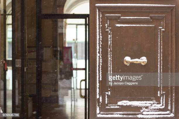 snow on opened wooden door - jacopo caggiano stock pictures, royalty-free photos & images