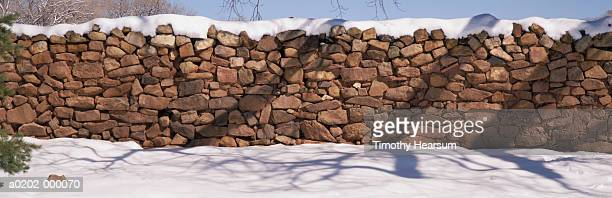 snow on stone wall - timothy hearsum stock photos and pictures