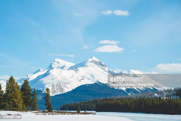 snow on the lake and snow-capped rugged mountains peaks in jasper national park - unesco stock-fotos und bilder
