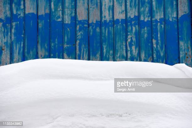 snow overhang on roof with blue wall - heap stock pictures, royalty-free photos & images