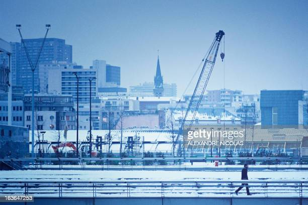 Snow paris buildings man walks alone blue tone bnf