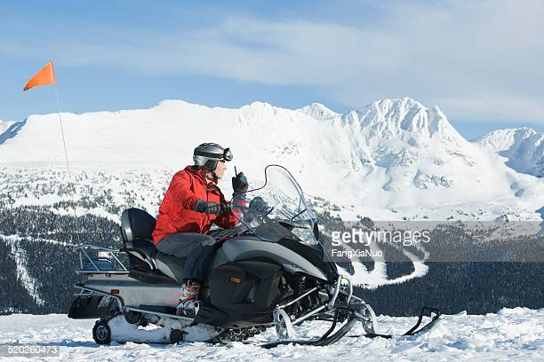 snow patrol rescue worker sitting on snowmobile, using walkie talkie - rescue worker stock pictures, royalty-free photos & images