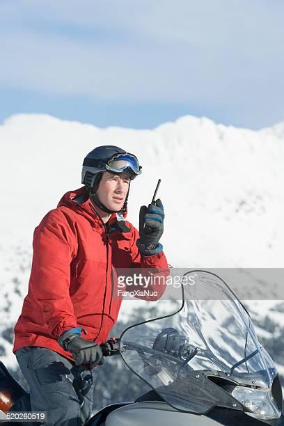 Snow patrol rescue worker, auf dem Schneemobil, mit walkie-talkie
