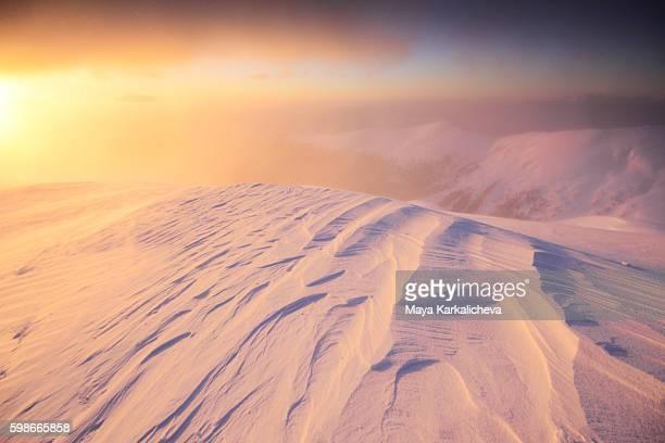 Snow pattern at sunrise on mountain peak