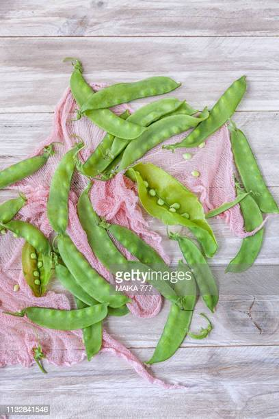 Snow peas also called sugar snap peas or mangetout on a rustic white wooden table.