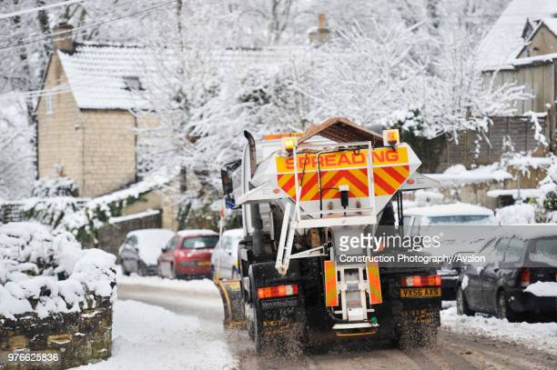 Snow plough and gritter in snowy weather, England, UK.