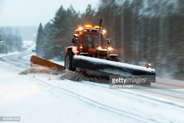 Snow plough clearing snow from road