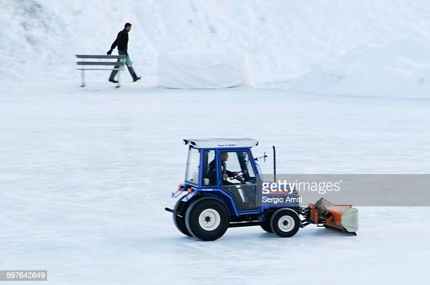 a snow plough clearing snow on a hockey rink - schneefahrzeug stock-fotos und bilder