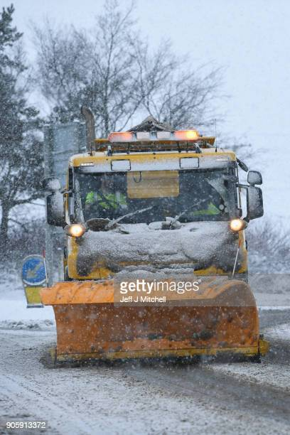 A snow plough clears snow on a slip road next to the M74 following motorist spending the night stranded on the motorway on January 17 2018 in...