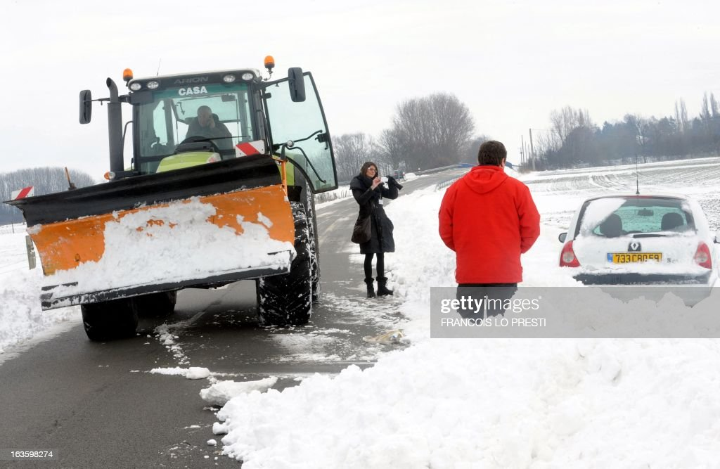 A snow plough drives past people taking picture of a car blocked by snow on the side of a road on March 13, 2013 in the northern French city of Estreux. Blizzard-like conditions, coming only eight days before the official start of spring, knocked out power to thousands of people in France and left motorists stranded in their cars.