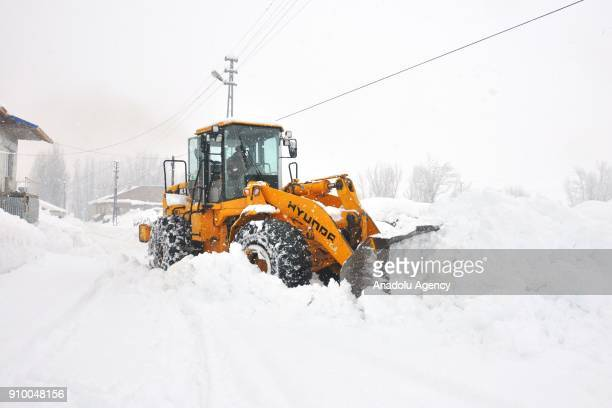 A snow plow clears huge piles of snow after a heavy snow fall in Ovacik town of Tunceli Turkey on January 25 2018