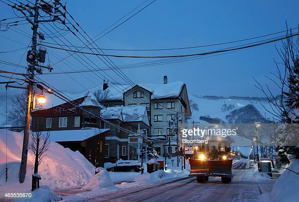 A snow plow drives on a street in the Hirafu area of Kutchan Hokkaido Japan on Sunday Feb 15 2015 The ski and snowboard resort majority owned by...