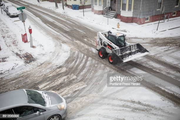 A snow plow drives through Portland's West End Tuesday morning