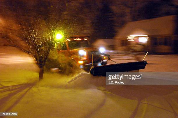 Snow plow negotiates a side street covered in snow December 8 in Bowling Green, Ohio. Four to six inches of snow is predicted to fall overnight,...